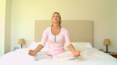 Young woman relaxing with yoga on bed — Stock Video