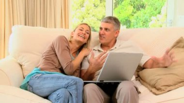 Happy couple relaxing with laptop — Stock Video