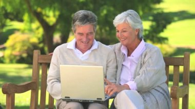 Mature couple surfing on their laptop oudoors — Stock Video