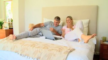 Attractive couple relaxing on bed with laptop — Stock Video