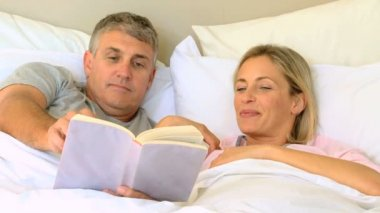 Couple in bed enjoying a book — Stock Video