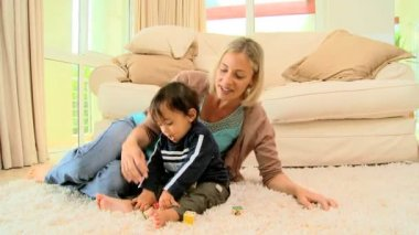 Mother with little boy playing alphabet blocks on carpet — Stock Video