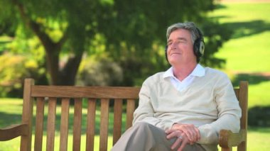 Mature man listening to music with his headphones — Stock Video