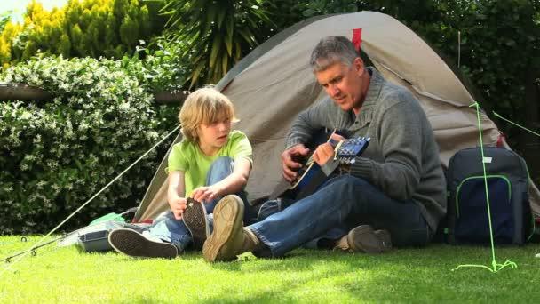 Adam oğluyla bahçede çadır dışında gitar çalmak — Vídeo de stock