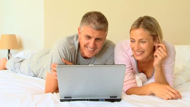 Pareja acostada en un ordenador portátil — Vídeo de stock