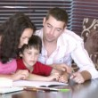 Parents helping their son with homework — Stock Video #23635365