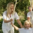 Parents help their son on a swing — Stock Video