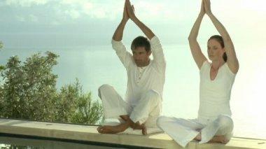 Twee personen doen yoga met zee op de achtergrond — Stockvideo