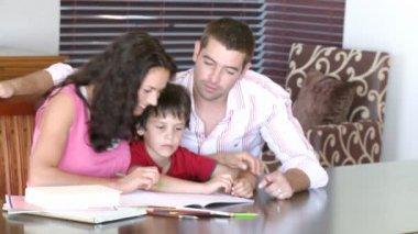 родители, помогая их сына с заданием — Стоковое видео