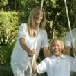 Happy Parents help their son on a swing — Stok video
