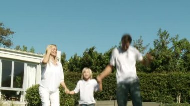 Parents and Child jumping on a trampoline — Stock Video