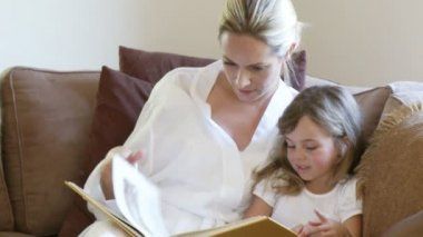 Relaxed Mother with daughter reading a book — Stock Video