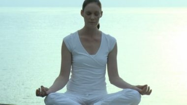 Woman doing Yoga with the sea in the background — Vídeo Stock