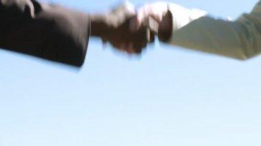 Twee zakenmensen schudden handen - multi culturele — Stockvideo