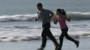 Two People Jogging along a Beach — ストックビデオ