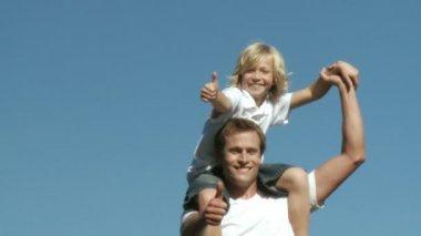 Padre cariñoso con su hijo sobre sus hombros con los pulgares para arriba — Vídeo de Stock
