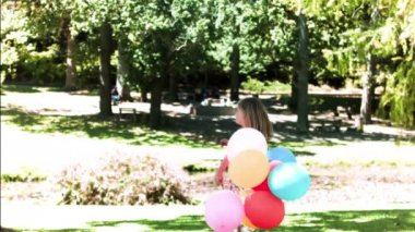 Child holding balloons in slow motion — Stock Video
