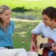 A man plays guitar and sings to a woman as they sit in the park — Stock Video