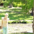 A woman walks up towards a tree talking on her phone — Stock Video