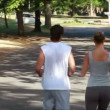 Two joggers jog down the road together as the camera zooms up behind them — Stock Video