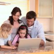 Family looking at a laptop together — Stock Video #23692013