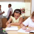 Brother and sister doing homework in the kitchen with parents behind them — Stock Video #23692211