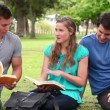 Man shows a book to his friends while smiling as they sit together in a park — Stock Video