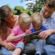 Family sitting next to each other while using a tablet pc which is being held by the children — Stock Video