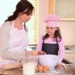 Mother helping her daughter to cook — Stock Video #23693969