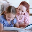 Cute child reading a book aloud with her mother — Stock Video