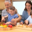 Stock Video: Smiling family preparing meal