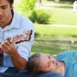 Man practises guitar as the woman rests on his leg and reads — Stock Video #23694421