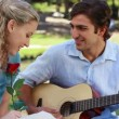 Stock Video: Boyfriend plays guitar for his girlfriend as she holds a rose and then kiss