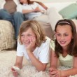 Stock Video: Siblings lying on the floor and watching tv with parents behind them