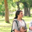 Camera pans to show two friends talking as they stand by the trunk of a tree in the park — Stock Video