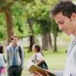 Man reading a book before looking at the camera while smiling as he stands in a park — Stock Video #23696273
