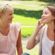 Stock Video: Two girls sit in park and pass phone back and forth while talking on it