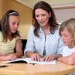 Mother helping her children with homework — Stock Video #23697093