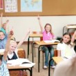 Pupils raising their fingers in front of the teacher — Stock Video #23697563