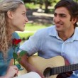 A man serenades his girlfriend with a song as she holds a rose as they look at the camera — Stock Video
