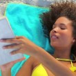 Stock Video: Tanned womreading novel