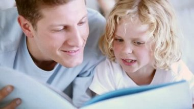 Child reading a book aloud with his father — Stock Video