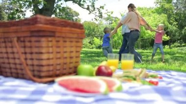 Family dancing in a cirlcle in the background with a platter on a picnic basket in the foreground — Stock Video