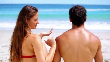 Brunette applying sunscreen on her boyfriend — Stock Video