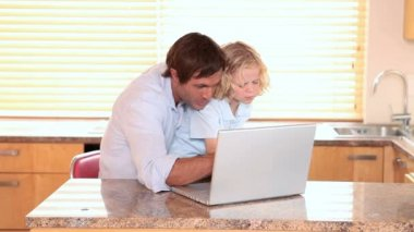 Smiling father and son using a laptop — Stock Video