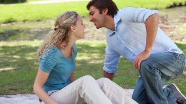 Un uomo si siede accanto alla sua ragazza e le dà un bacio prima che essi parlare insieme — Video Stock