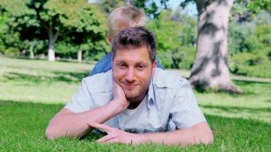 Babası oğlunun arkasından onu kafasını dışarı peeks önce çim üzerinde yalan ise geleceğe bakış — Stok video
