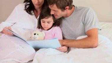 Família feliz, lendo um livro em voz alta — Vídeo stock