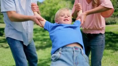 Boy being swung back and forth by his parents who are holding his arms — Stock Video