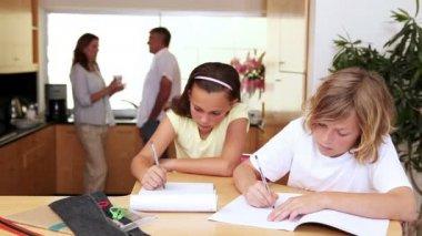 Fratello e sorella a fare i compiti in cucina con i genitori alle loro spalle — Video Stock